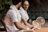 retro styled tennis players resting on chairs with towels and rackets at tennis court