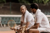 retro styled tennis players sitting on chairs with towels and rackets at tennis court