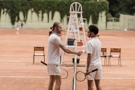 Photo pour Vue latérale des tennismen style rétro se serrant la main au-dessus de tennis net à court - image libre de droit