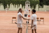 side view of retro styled tennis players shaking hands above tennis net at court