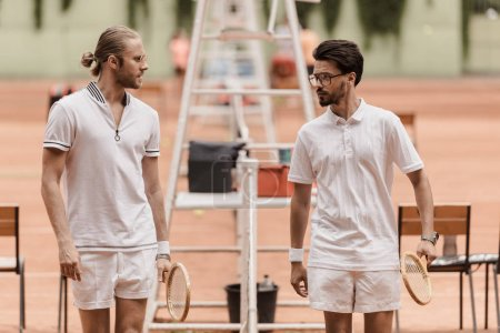 retro styled tennis players walking and looking at each other before game at tennis court