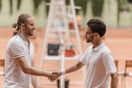 Photo pour Vue latérale des tennismen style rétro se serrant la main avant match au court de tennis - image libre de droit