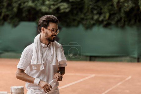 smiling handsome tennis player holding bottle of water at tennis court