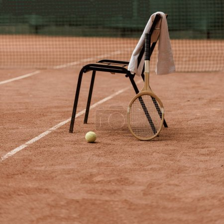chair with towel and tennis racket with tennis ball at court