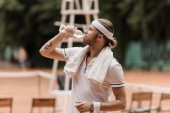 side view of handsome retro styled tennis player drinking water at tennis court