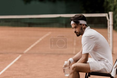 side view of retro styled tennis player sitting on chair with bottle of water at tennis court