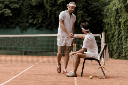 retro styled tennis players shaking hands at tennis court