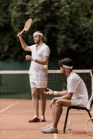 retro styled tennis players preparing for game at tennis court