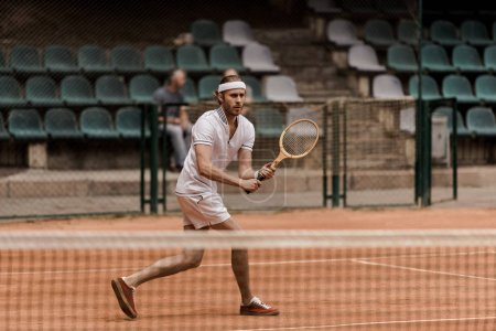 Photo for Concentrated retro styled man playing tennis at court - Royalty Free Image