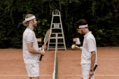 side view of retro styled tennis players starting game at tennis court
