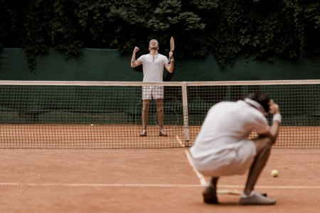 retro styled tennis player showing yes gesture after winning game at tennis court