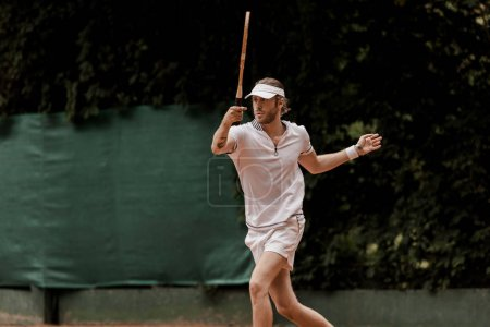 Photo for Handsome retro styled man playing tennis at court - Royalty Free Image