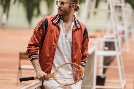 handsome retro styled tennis player standing with tennis racket at court