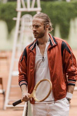 Photo pour Beau rétro style tennisman permanent avec une raquette au court de tennis et à la recherche. - image libre de droit