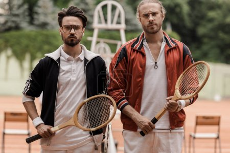 serious retro styled tennis players looking at camera at tennis court