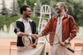 happy retro styled tennis players shaking hands at tennis court