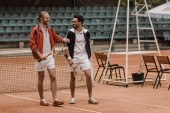 sourire des tennismen beau marcher et l'autre en regardant à la Cour