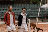 handsome retro styled tennis players walking with rackets at tennis court