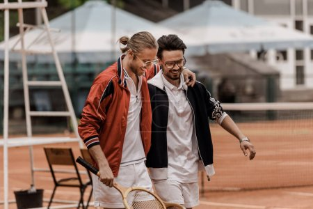 smiling retro styled tennis players walking with rackets and hugging at tennis court