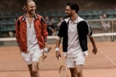 smiling retro styled tennis players walking and looking at each other at tennis court