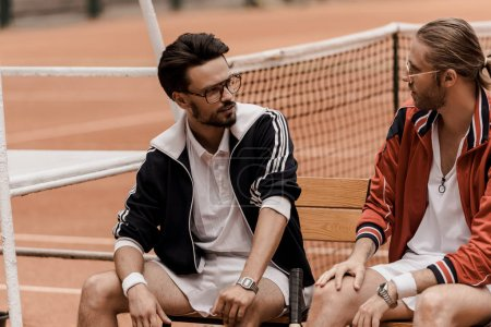retro styled tennis players sitting on chairs at tennis court and looking at each other