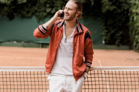 smiling retro styled tennis player talking by smartphone at tennis court