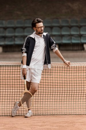 handsome retro styled tennis player leaning on tennis net at court and looking away
