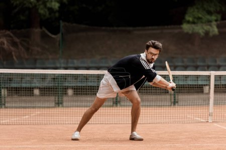 Photo for Retro styled handsome tennis player playing tennis - Royalty Free Image