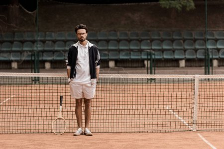 handsome retro styled tennis player standing at tennis court and looking at camera
