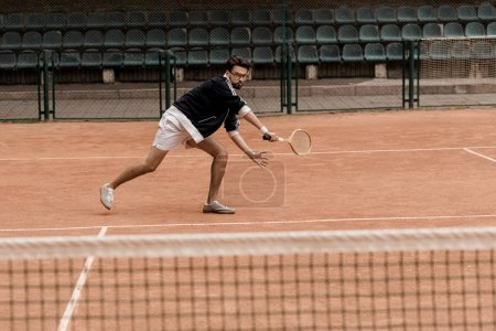 retro styled handsome man playing tennis with racket at tennis court