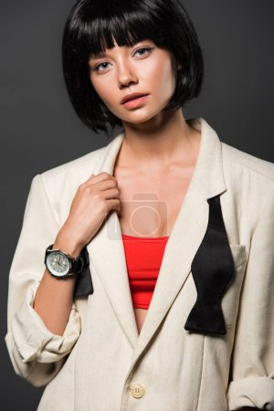 attractive young woman in stylish beige jacket looking at camera isolated on grey