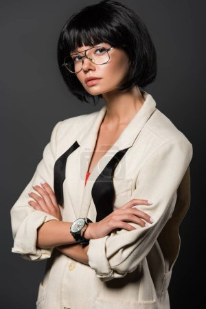 attractive young woman with crossed arms in stylish jacket looking at camera isolated on grey