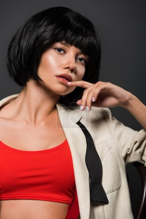 close-up portrait of young woman in stylish jacket over red crop top looking at camera isolated on grey