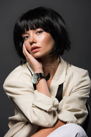 close-up portrait of young woman in stylish jacket with male wrist watch isolated on grey