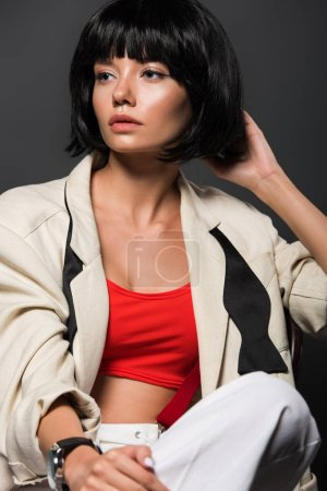 beautiful young woman in stylish jacket looking away isolated on grey