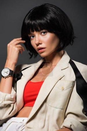 Photo pour Jeune femme séduisante dans des vêtements élégants, regardant la caméra isolée sur fond gris - image libre de droit