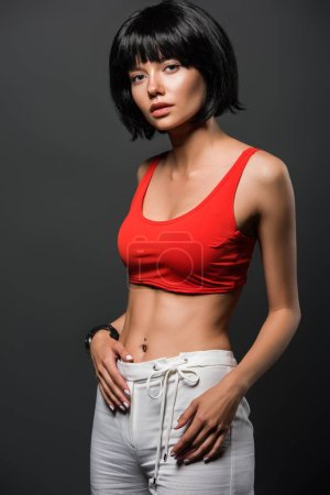 slim young woman in red crop top looking at camera isolated on grey