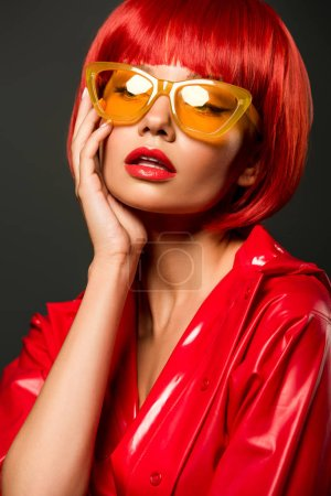 Photo for Close-up portrait of young woman in red latex jacket and vintage yellow eyeglasses isolated on grey - Royalty Free Image