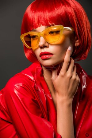 Photo for Close-up portrait of fashionable young woman in red latex jacket and vintage yellow sunglasses isolated on grey - Royalty Free Image