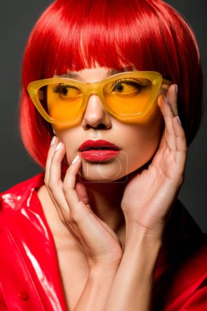 close-up portrait of beautiful young woman in red latex jacket and vintage yellow sunglasses isolated on grey