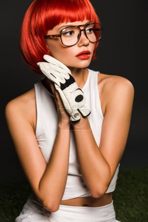 seductive young woman with red bobbed haircut in golf glove and stylish eyeglasses looking away on grey