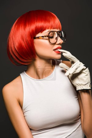 seductive young woman with red bob cut in golf glove and stylish eyeglasses isolated on grey