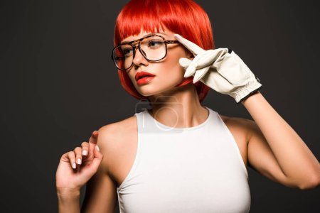 beautiful young woman with red bob cut in golf glove and stylish eyeglasses isolated on grey