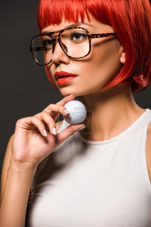 close-up portrait of attractive young woman with red bob cut and stylish eyeglasses holding golf ball isolated on grey