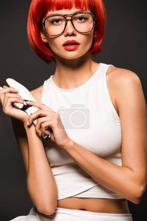 beautiful young woman with red bob cut in golf glove and stylish eyeglasses looking at camera isolated on grey