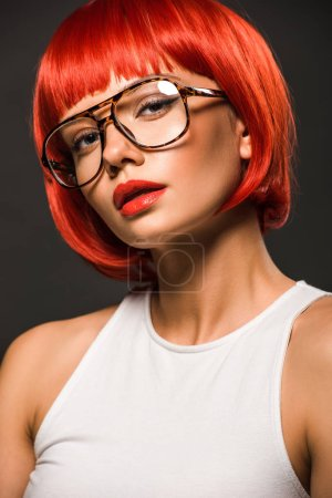 attractive young woman with red bob cut and stylish eyeglasses looking at camera isolated on grey