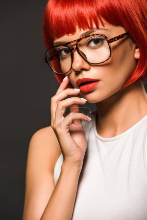 beautiful young woman with red bob cut and stylish eyeglasses looking at camera isolated on grey