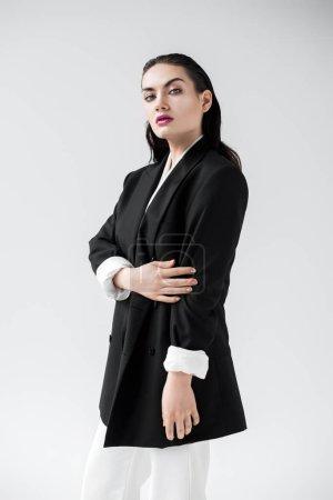seductive fashionable model posing in black jacket, isolated on grey
