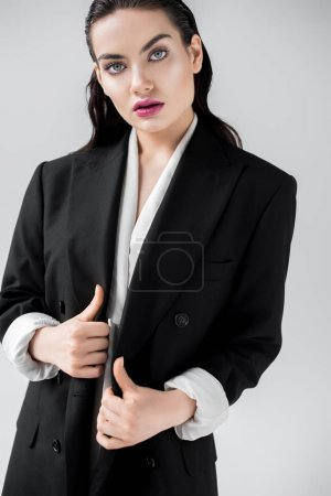 beautiful elegant woman posing in black fashionable jacket, isolated on grey
