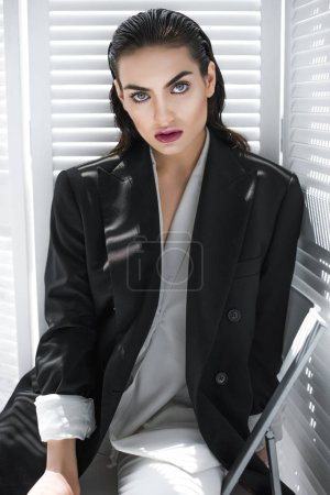 elegant fashionable girl with makeup posing in black jacket